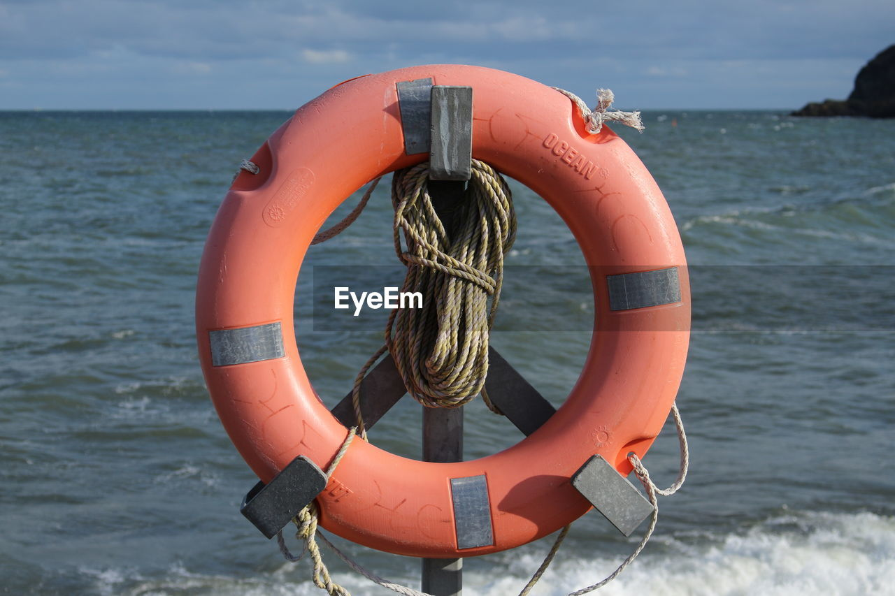 water, life belt, sea, safety, security, rescue, protection, orange color, sky, circle, nature, rope, tubing, shape, no people, day, buoy, geometric shape, inflatable, horizon over water, outdoors, floating on water