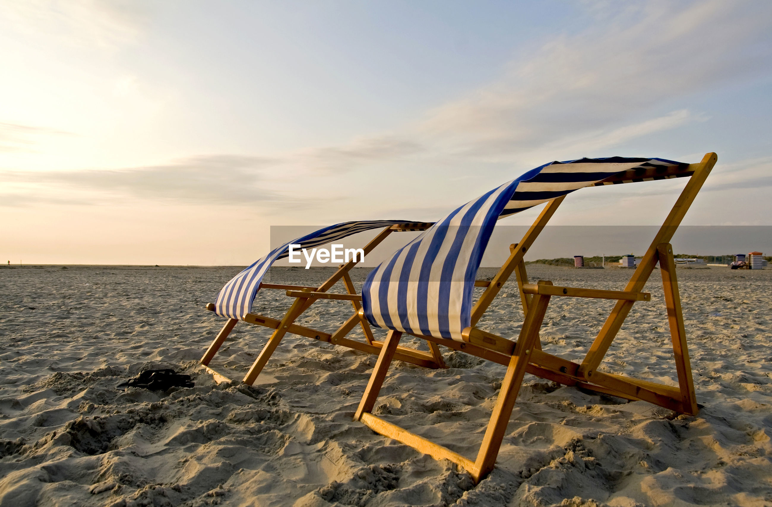 Deck chairs at beach against sky during sunset