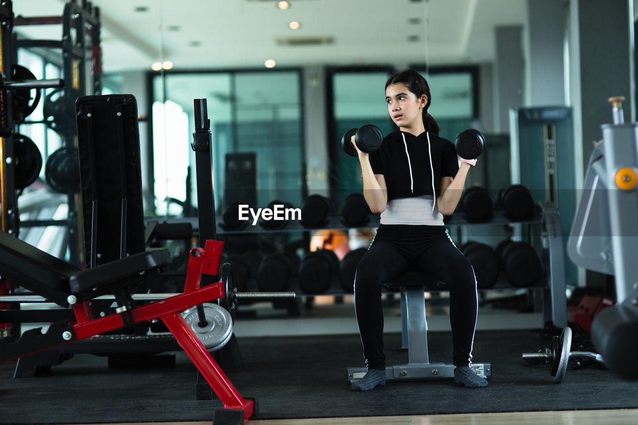 Full length of girl exercising in gym
