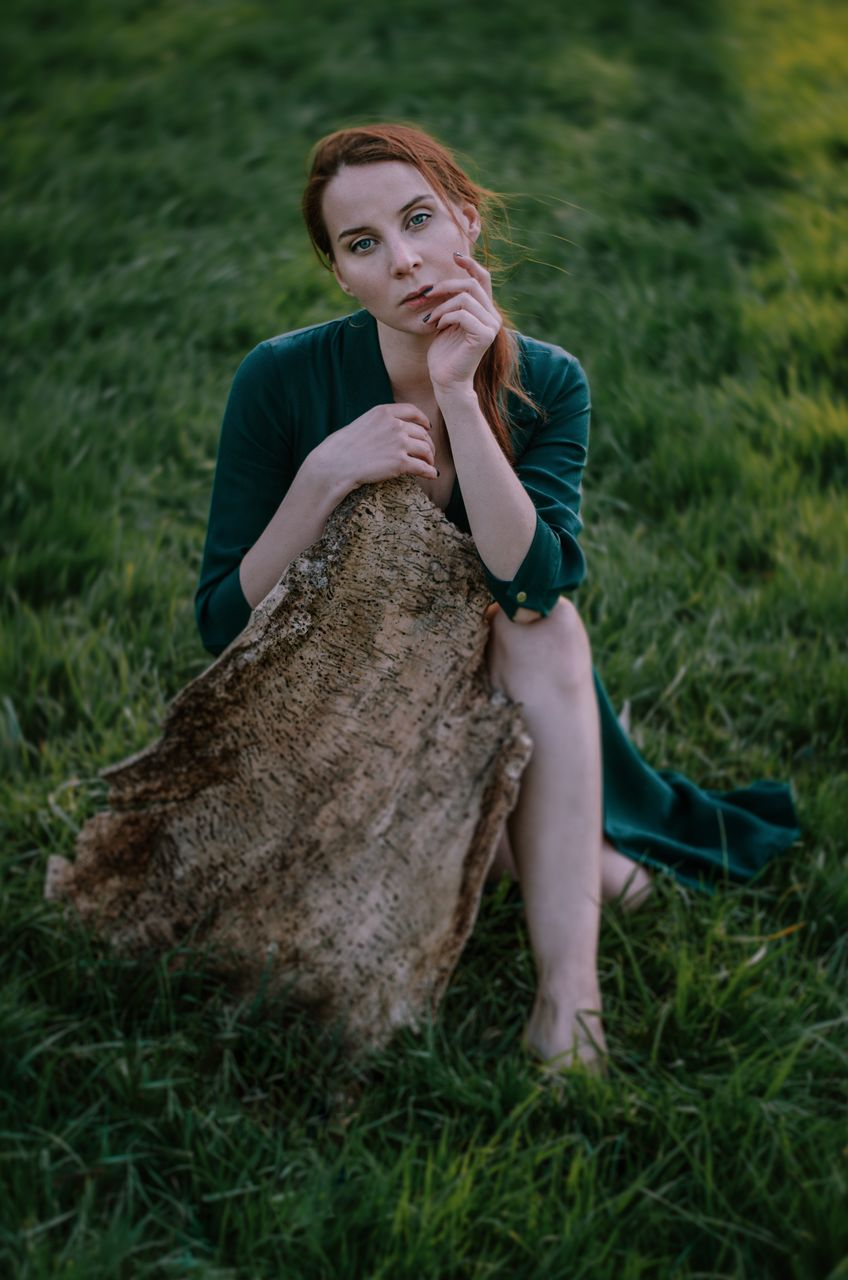 grass, leisure activity, young adult, real people, plant, field, land, casual clothing, lifestyles, young women, looking at camera, nature, one person, portrait, full length, sitting, green color, front view, outdoors, beautiful woman, hairstyle