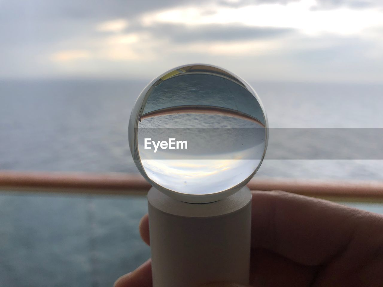 human hand, hand, human body part, real people, holding, one person, water, sea, unrecognizable person, sky, day, personal perspective, close-up, nature, body part, finger, lifestyles, glass - material, human finger, outdoors, horizon over water