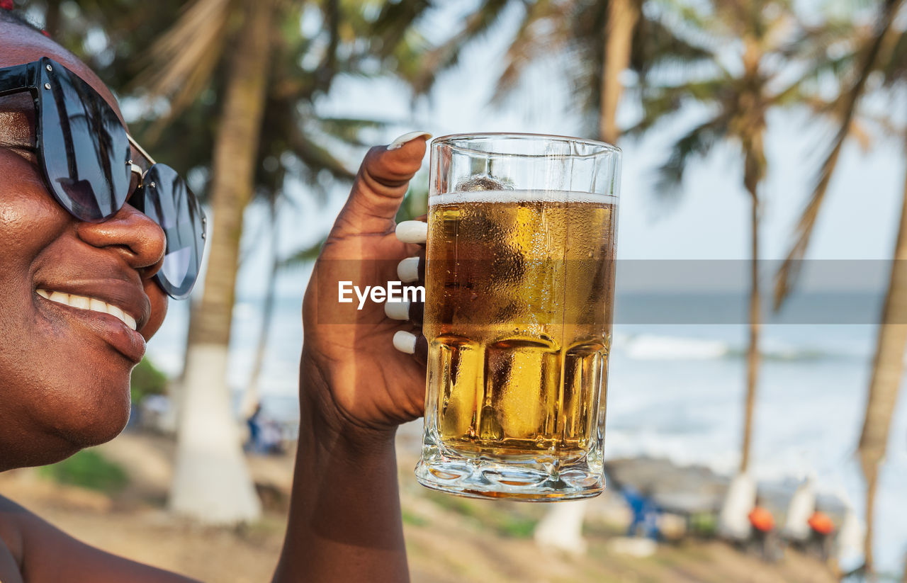 African happy woman drinking a beer out at a beach bar in accra ghana