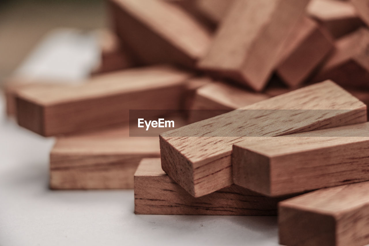 wood - material, indoors, large group of objects, toy block, still life, close-up, stack, no people, selective focus, toy, block, shape, design, block shape, focus on foreground, table, cube shape, high angle view, pattern, wood