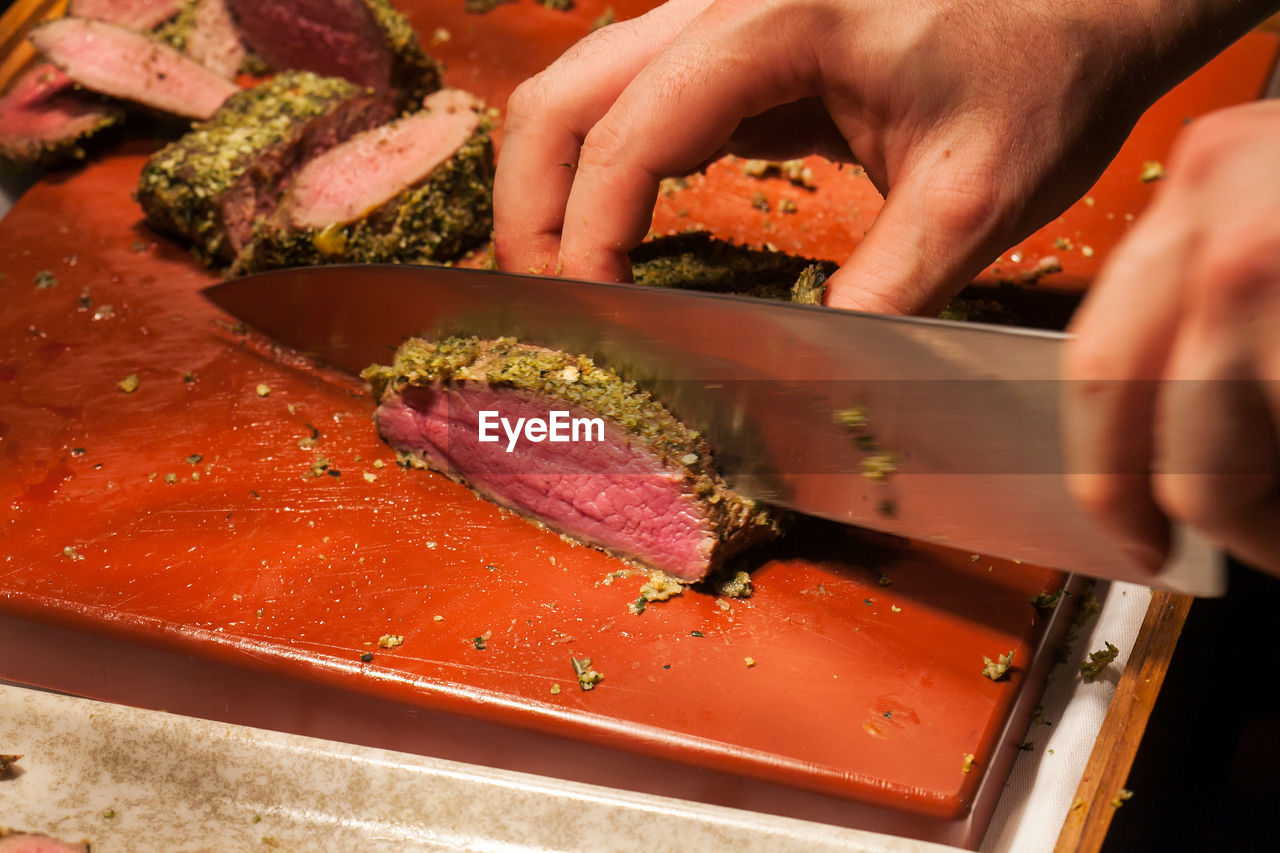 CLOSE-UP OF HAND HOLDING MEAT IN COOKING PAN