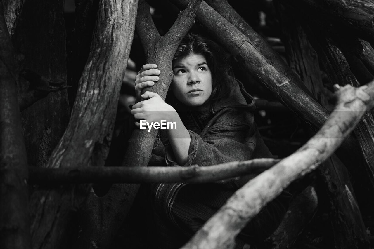 Young Woman Looking Up While Hiding Behind Firewood In Forest