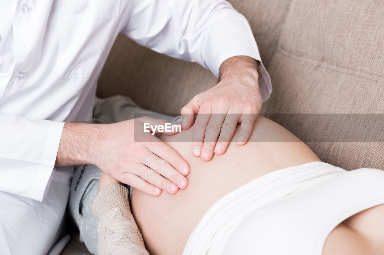 MIDSECTION OF MAN TOUCHING WOMAN LYING DOWN