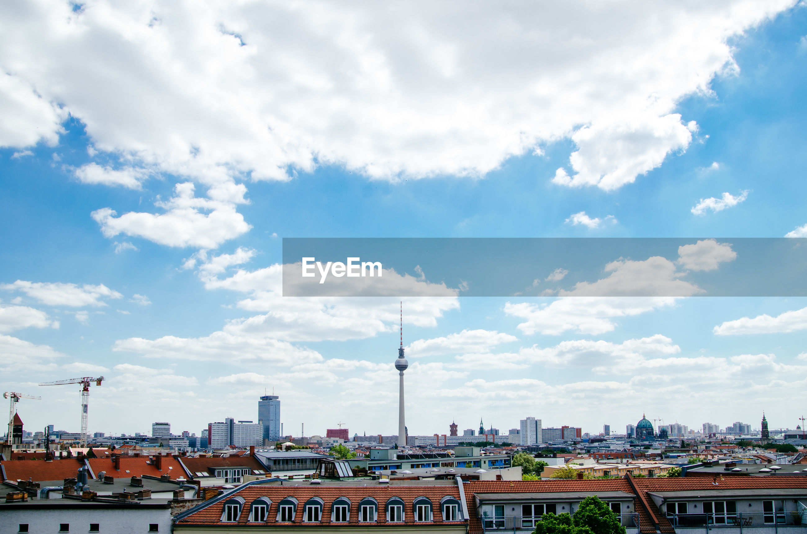 Fernsehturm amidst buildings in city against cloudy sky