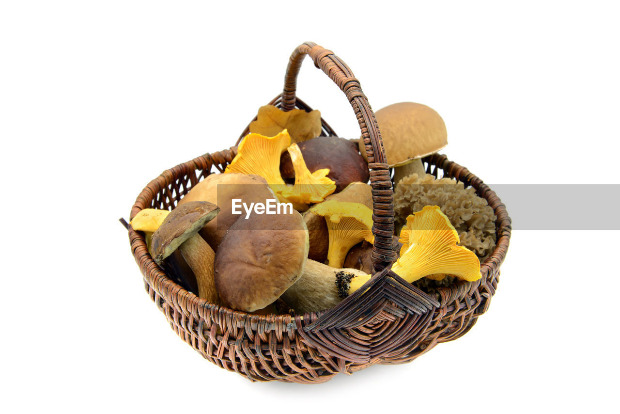 Close-Up Of Mushrooms In Wicker Basket Over White Background