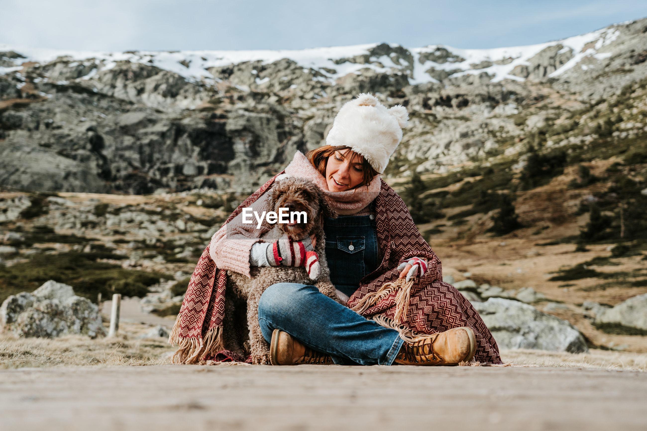 FULL LENGTH OF FRIENDS SITTING ON SNOW