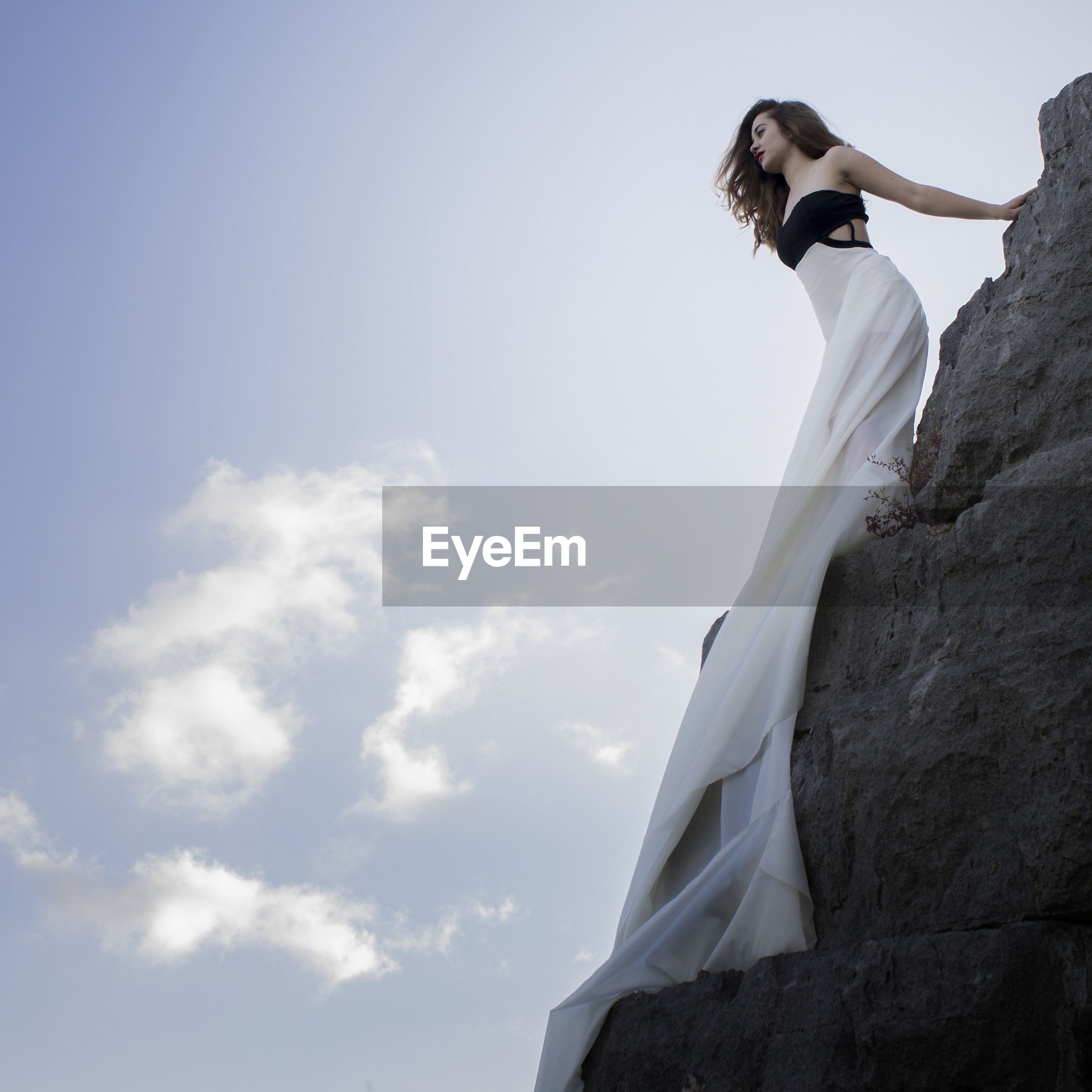 Low angle view of woman in evening gown standing on rock against sky