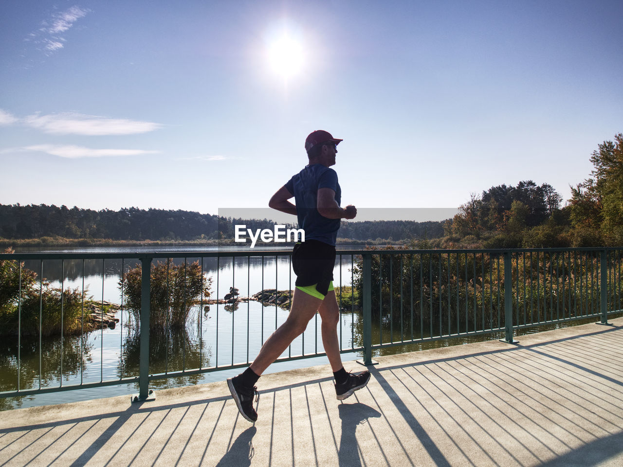 Man is training in the nature with sun behind him. young man on morning run outdoors.