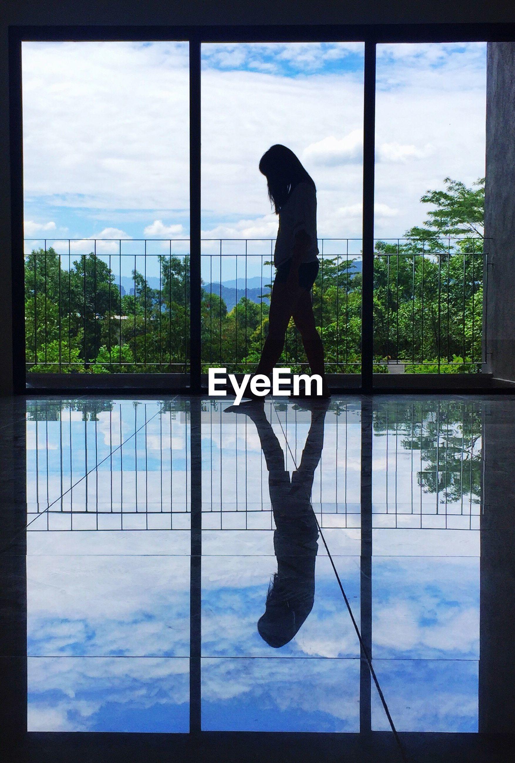 Side view of woman walking by window in building