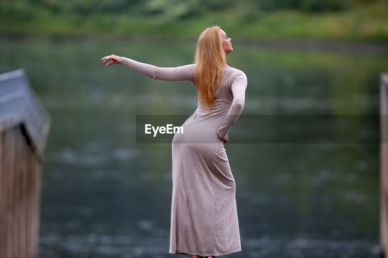 REAR VIEW OF WOMAN STANDING AT WATER