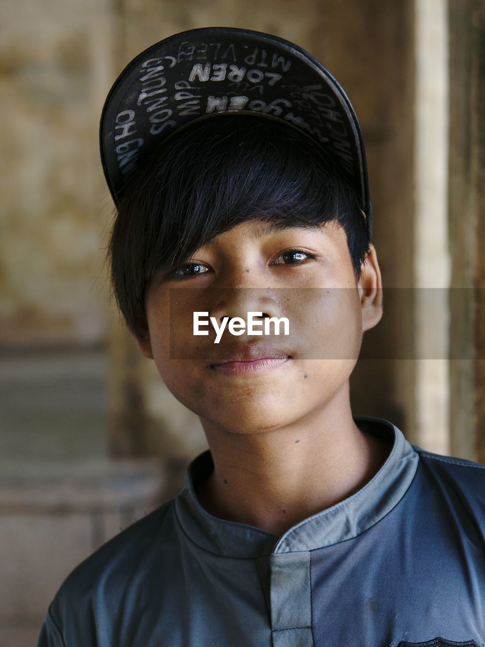 real people, headshot, one person, boys, portrait, looking at camera, focus on foreground, text, close-up, childhood, day, outdoors