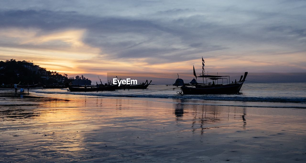 water, nautical vessel, sunset, transportation, mode of transport, sea, scenics, sky, moored, nature, beauty in nature, reflection, cloud - sky, tranquility, tranquil scene, waterfront, silhouette, no people, beach, outdoors, horizon over water, day