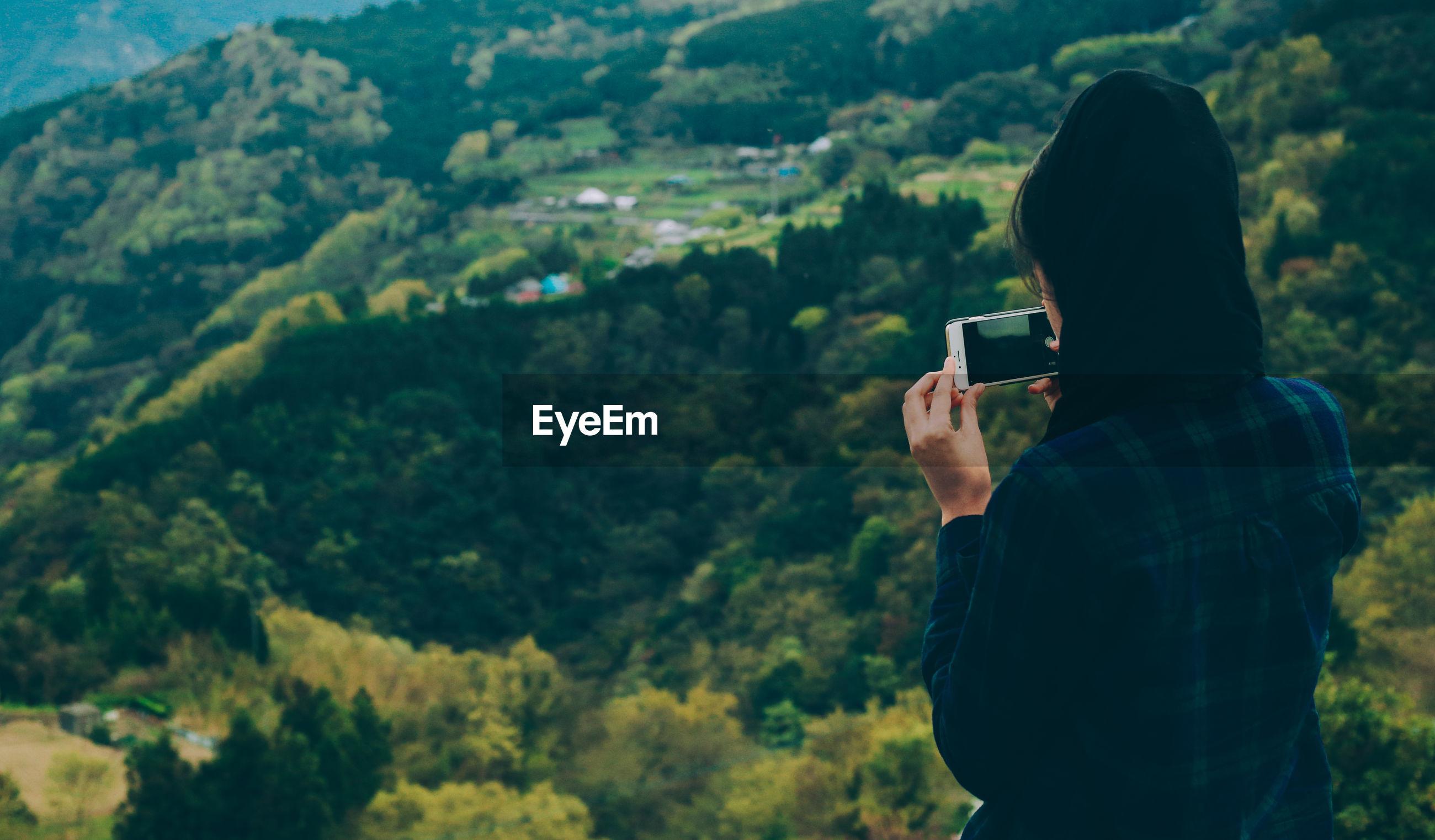 Woman photographing lush landscape
