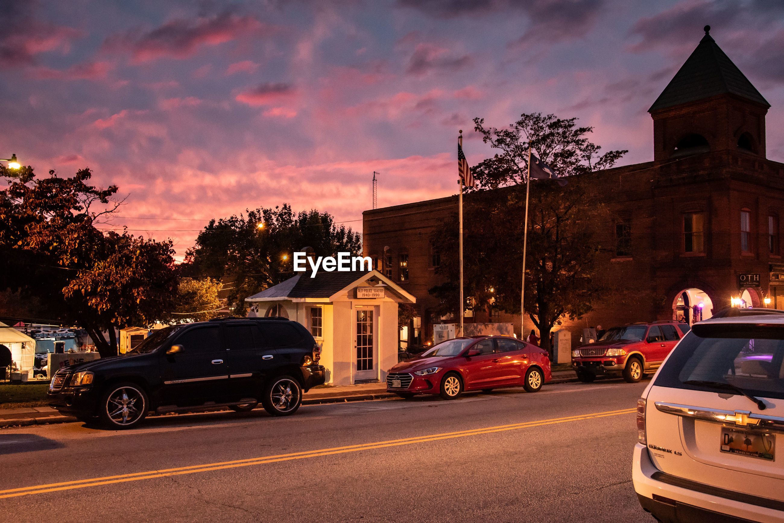 CARS ON ROAD BY ILLUMINATED BUILDINGS AGAINST SKY AT SUNSET