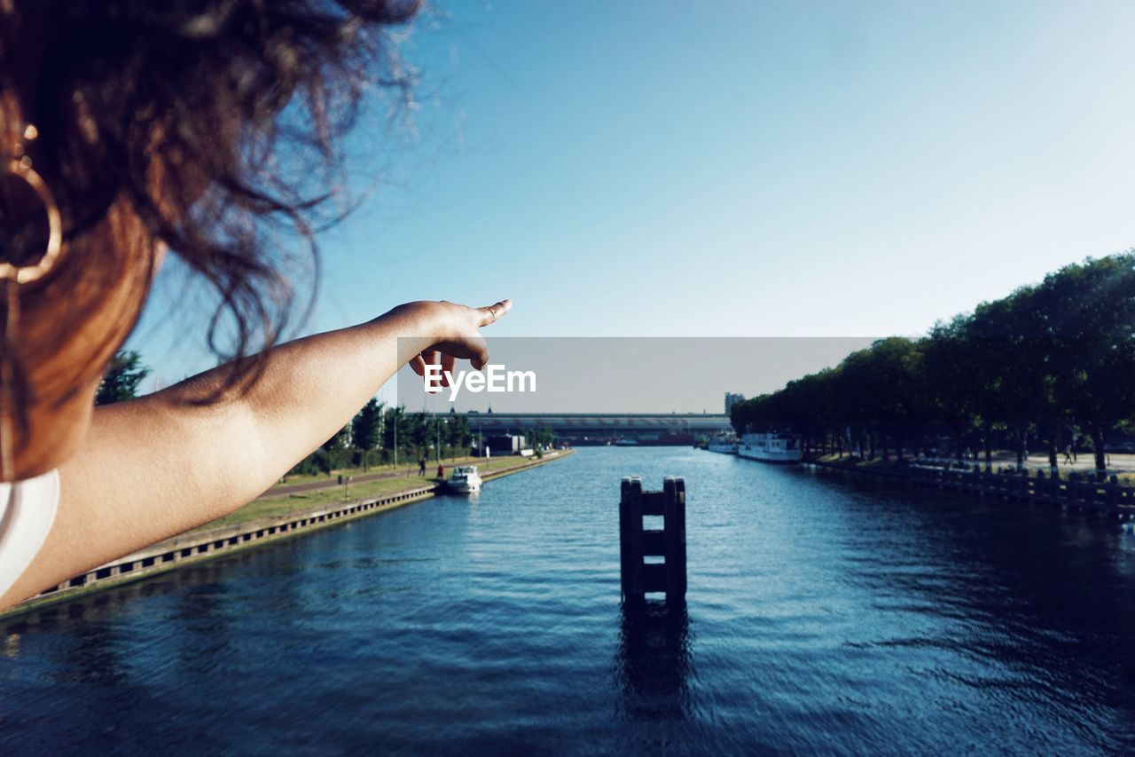 Midsection of woman gesturing over lake against clear sky
