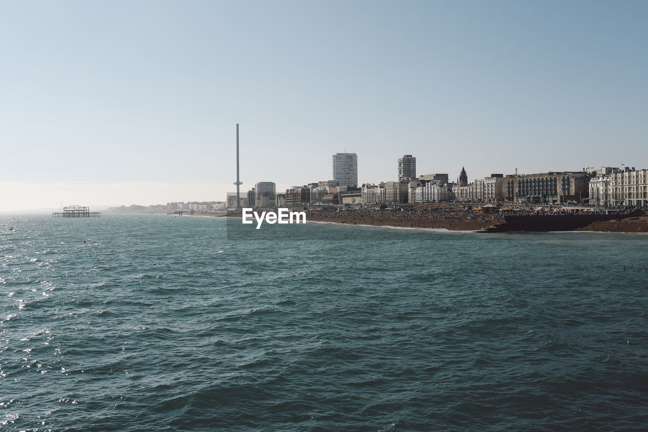 High Angle View Of Sea By Buildings Against Clear Sky