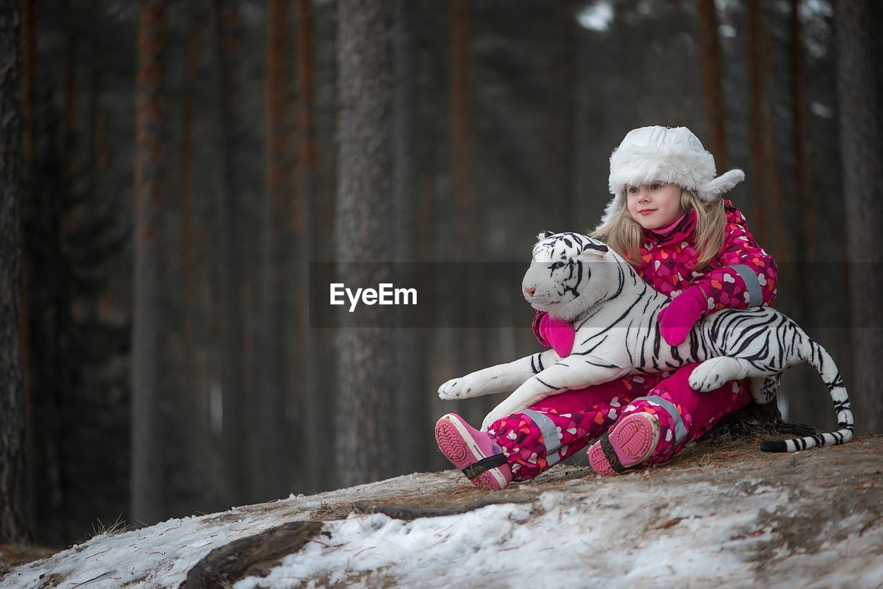 Portrait Of Smiling Girl Sitting On Snow
