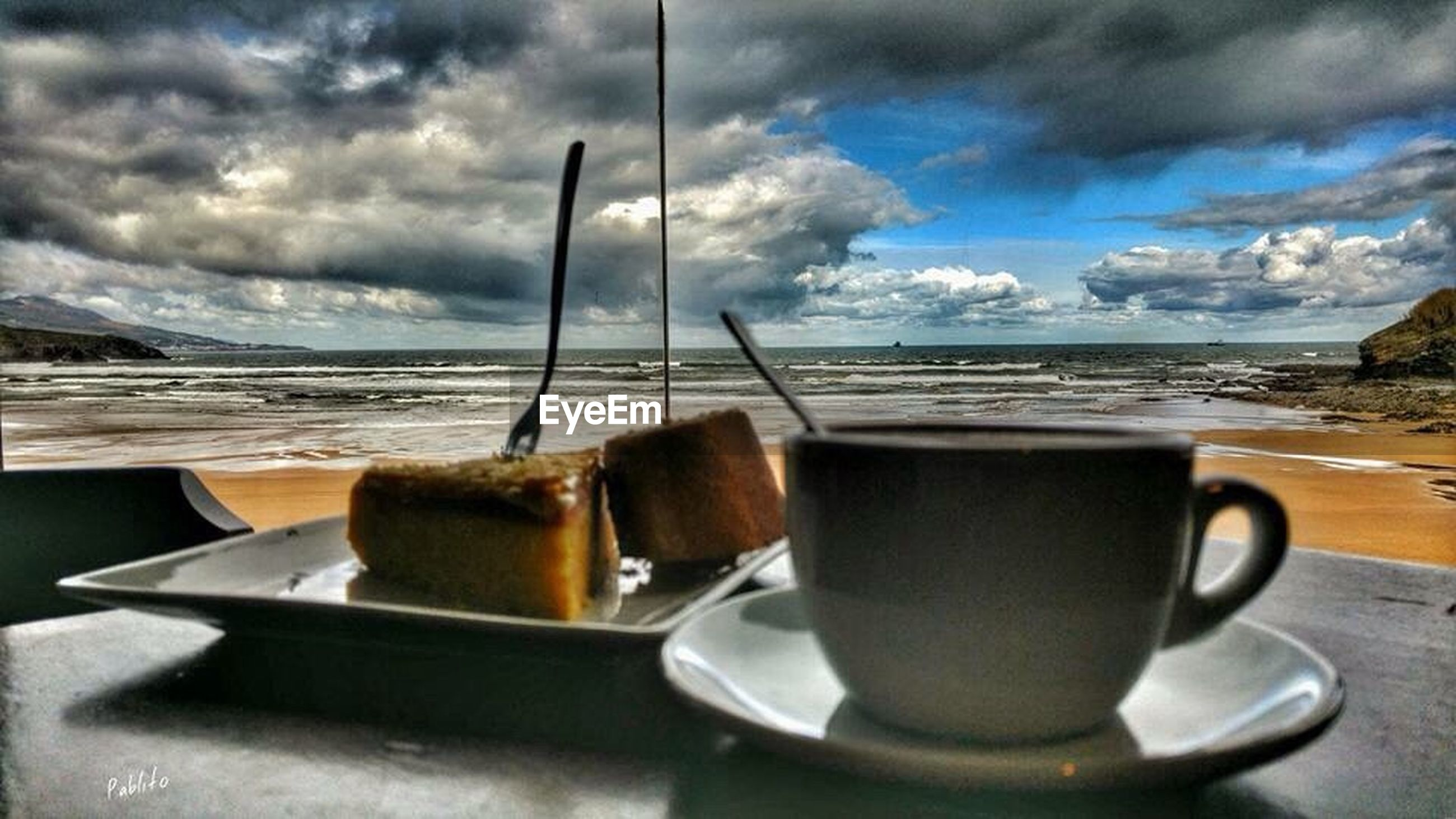 food and drink, drink, coffee cup, refreshment, table, sky, freshness, cloud - sky, coffee - drink, saucer, coffee, cloud, frothy drink, still life, sea, spoon, cup, cappuccino, indoors, beverage