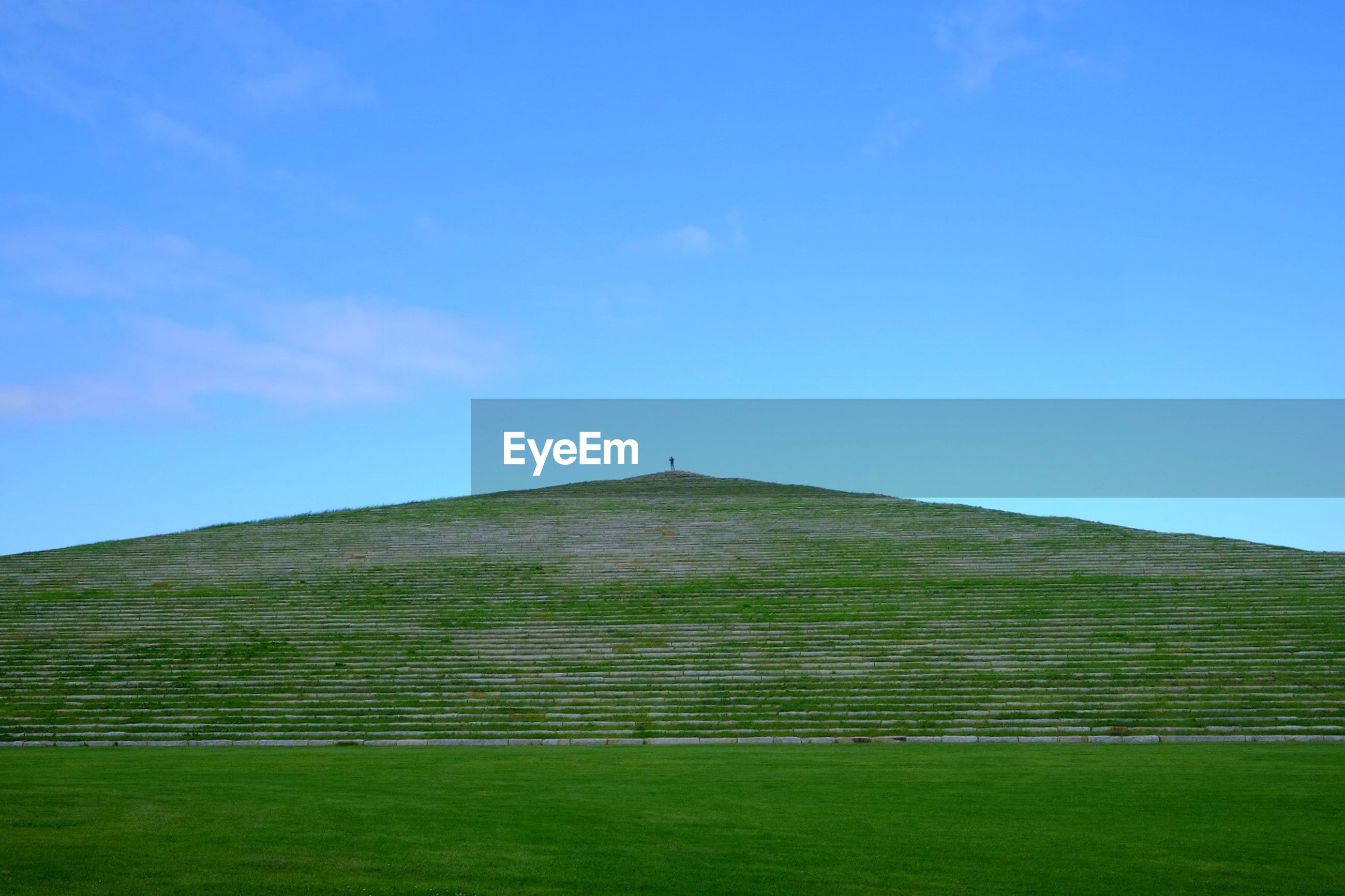 blue, built structure, architecture, grass, building exterior, sky, green color, clear sky, low angle view, copy space, field, landscape, day, outdoors, no people, nature, tranquility, tranquil scene, green, sunlight