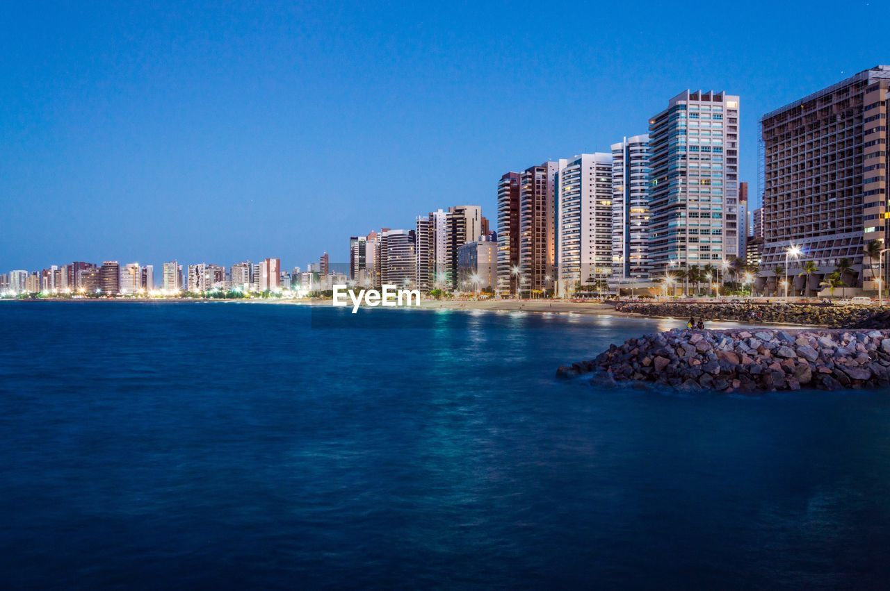 Sea By Illuminated City Against Clear Blue Sky