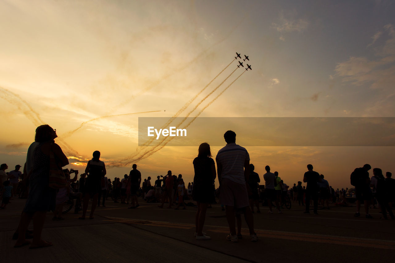 People watching airplane show against sky during sunset