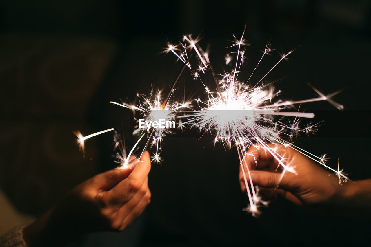 Cropped image of hands holding sparklers at night