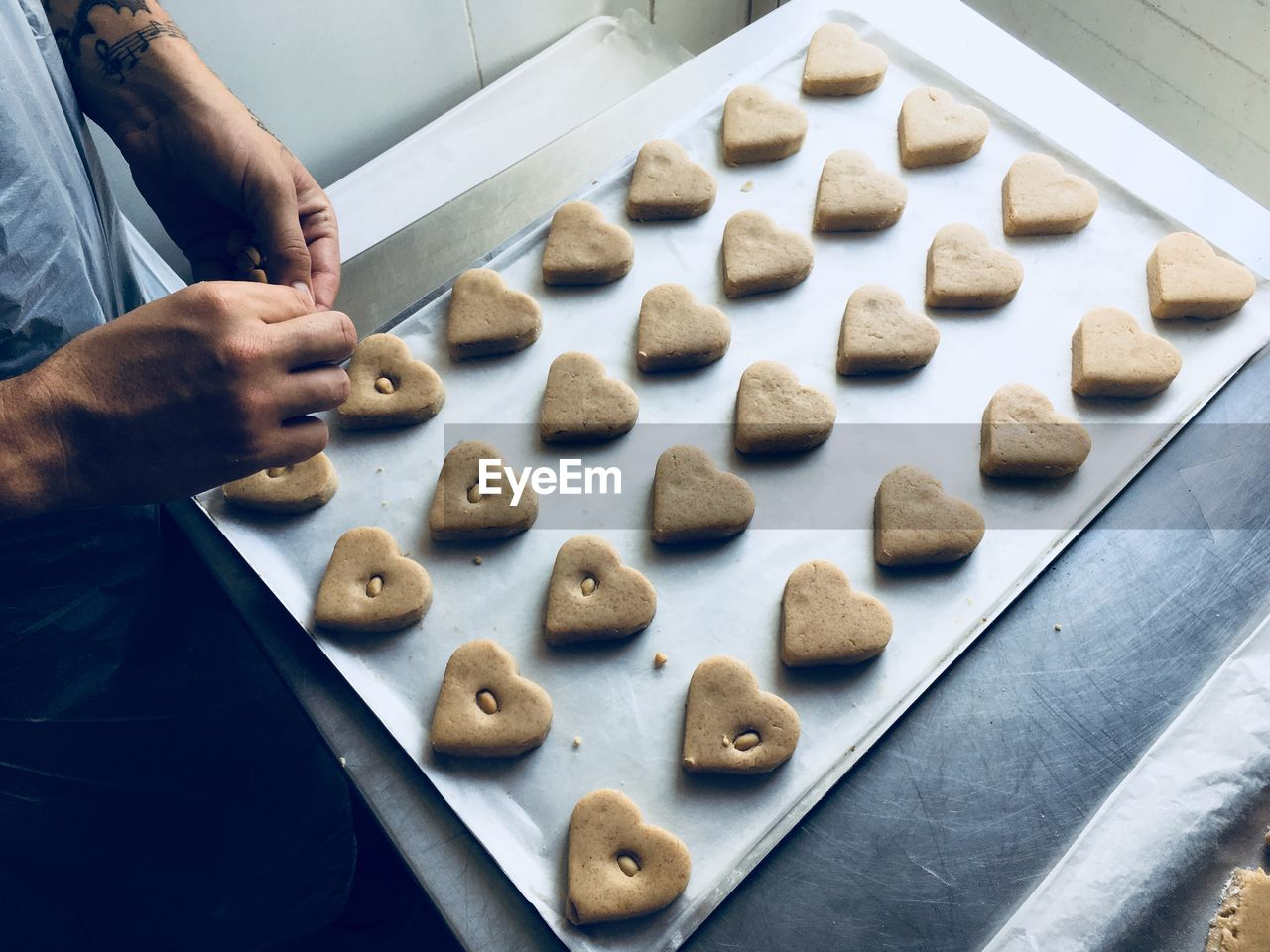 Midsection of male chef preparing heart shape cookies in kitchen