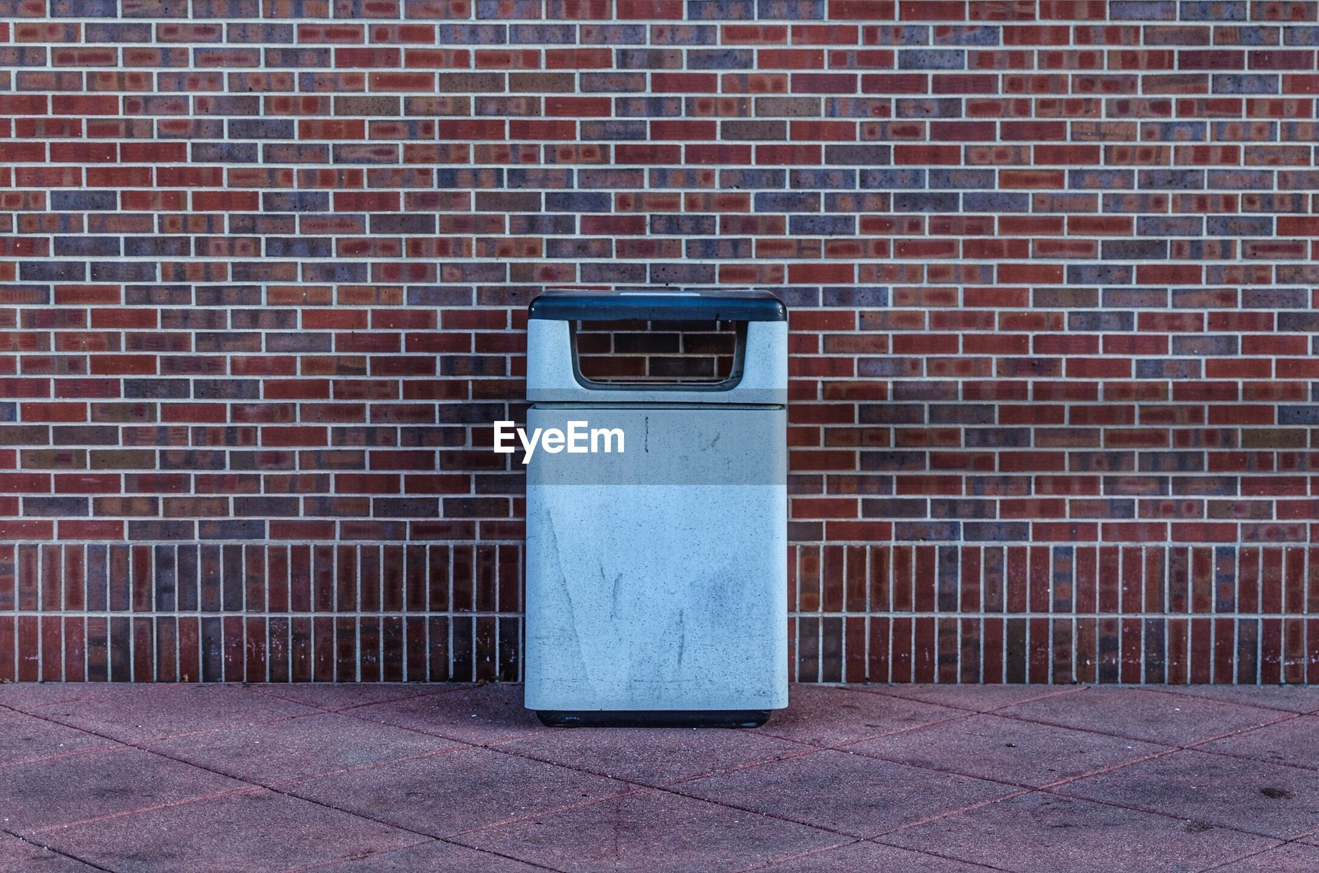 Garbage can on walkway against brick wall