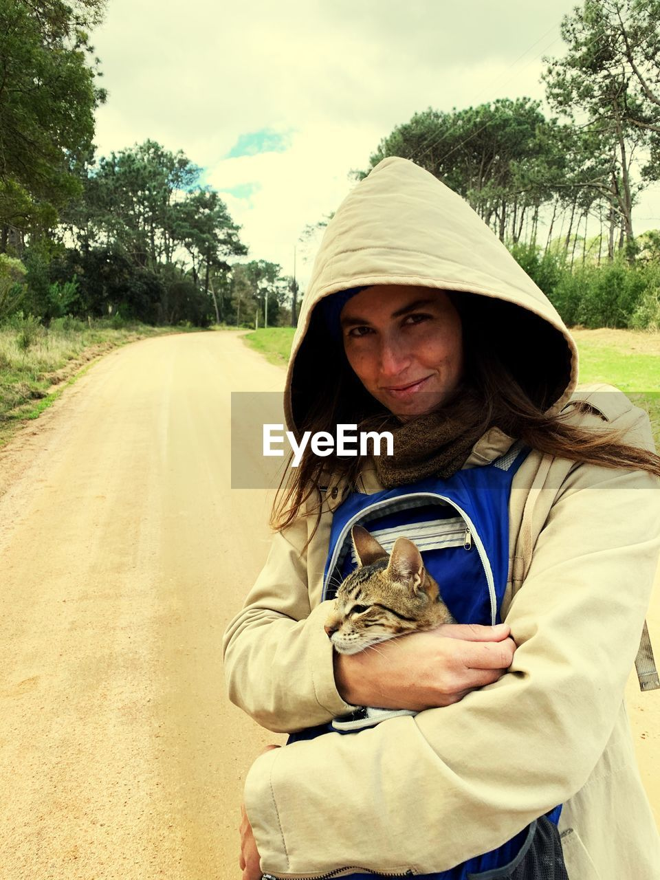 Portrait of woman embracing cat while standing on road