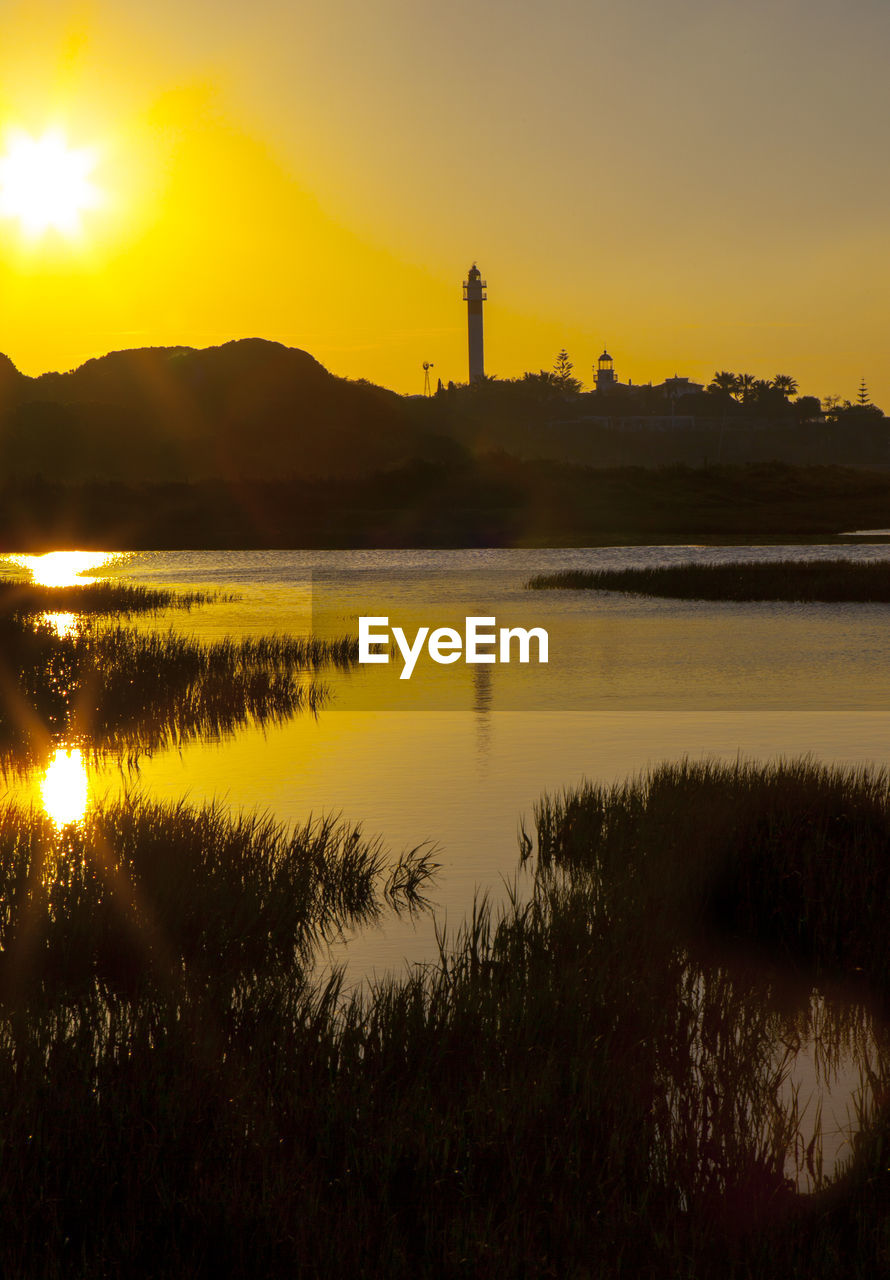 sky, sunset, reflection, water, nature, orange color, scenics - nature, no people, built structure, beauty in nature, building exterior, tranquility, architecture, tranquil scene, factory, plant, industry, tower, non-urban scene, outdoors, pollution