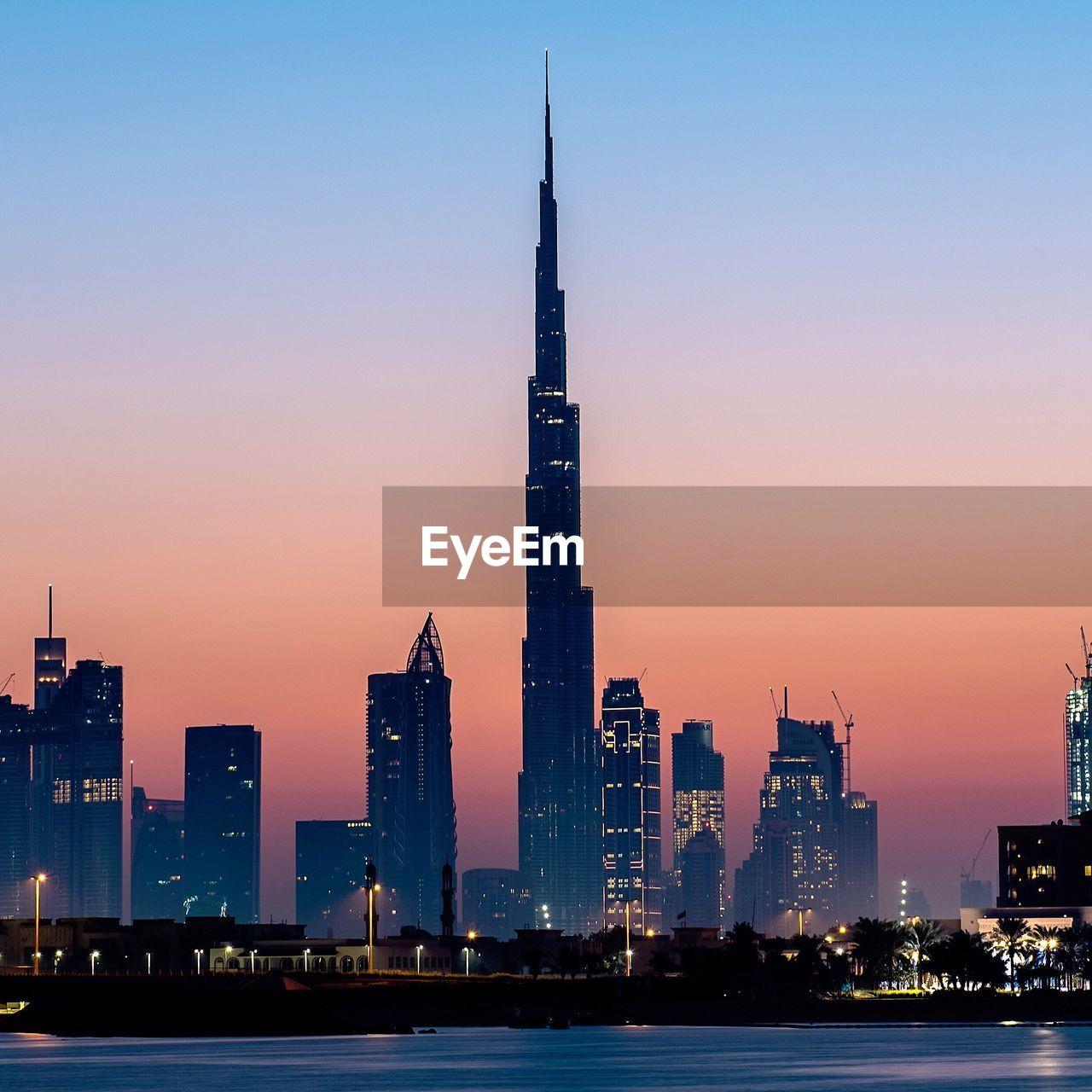 Illuminated Burj Khalifa Amidst Buildings In City Against Sky During Sunset