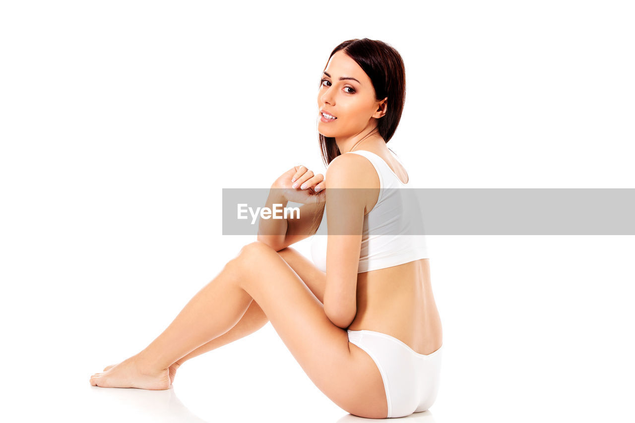 Portrait of sensuous young woman sitting on white background