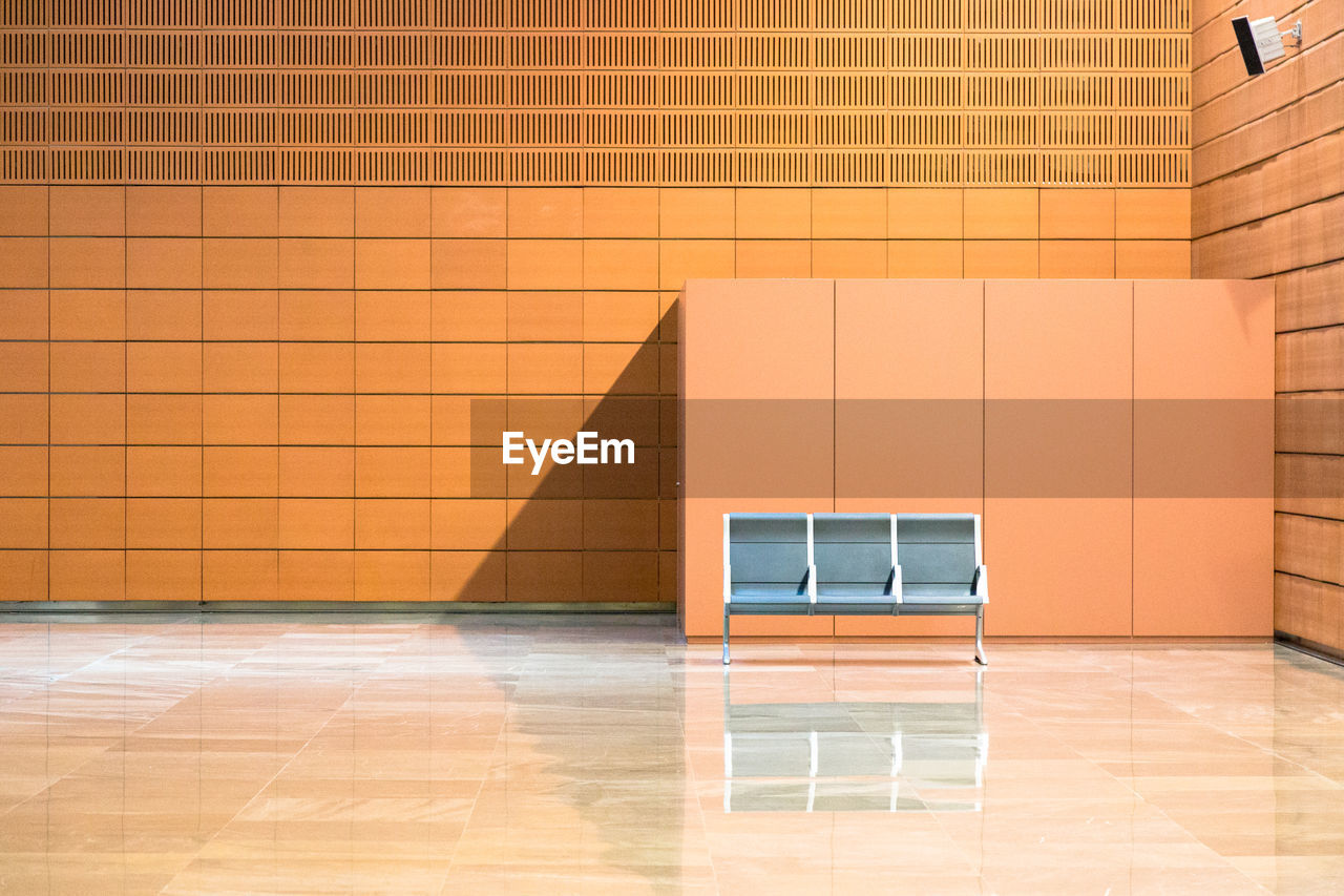 Empty Chairs Against Orange Wall