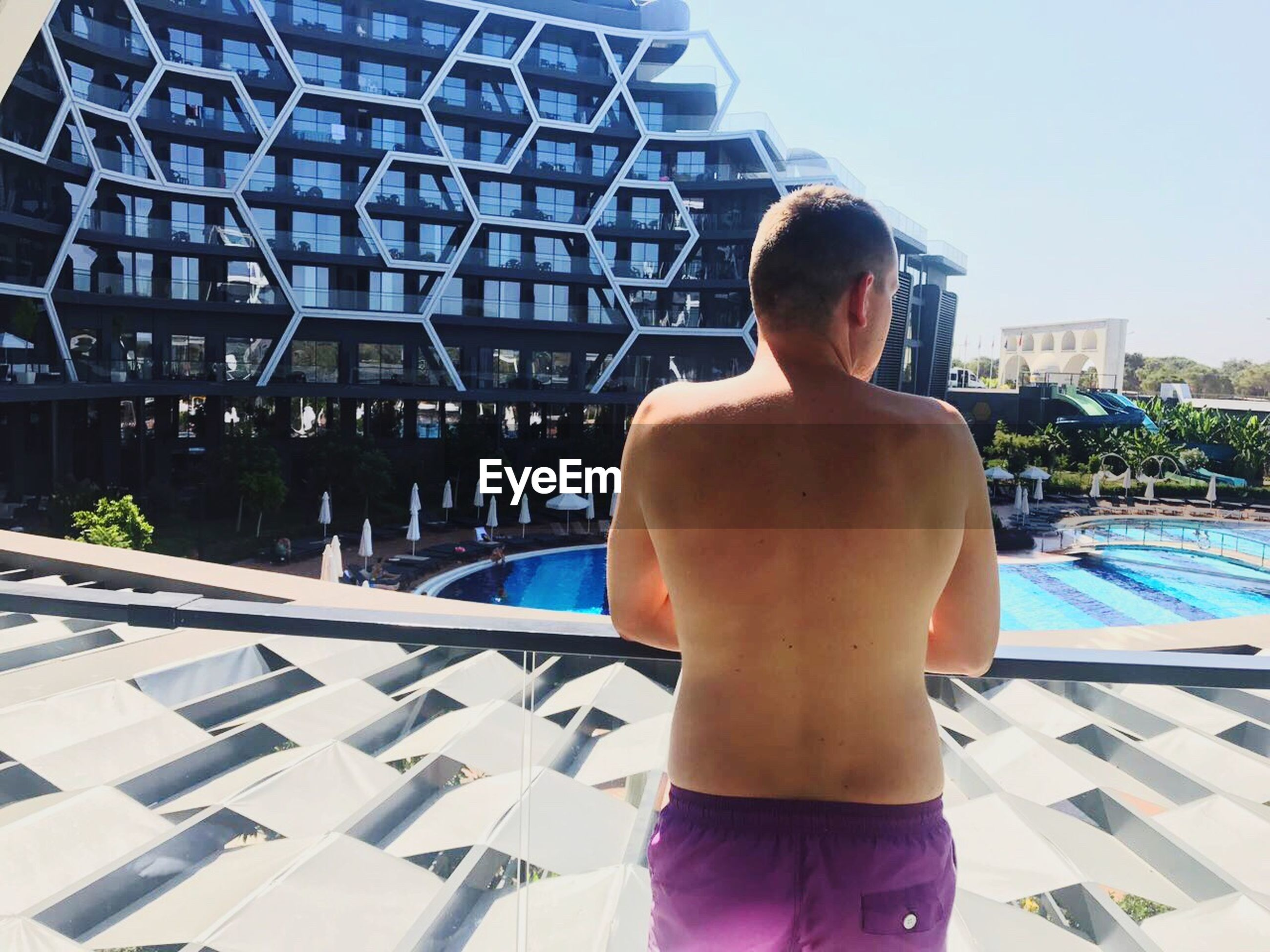 rear view, real people, lifestyles, leisure activity, swimming pool, water, summer, shirtless, one person, outdoors, day, architecture, people