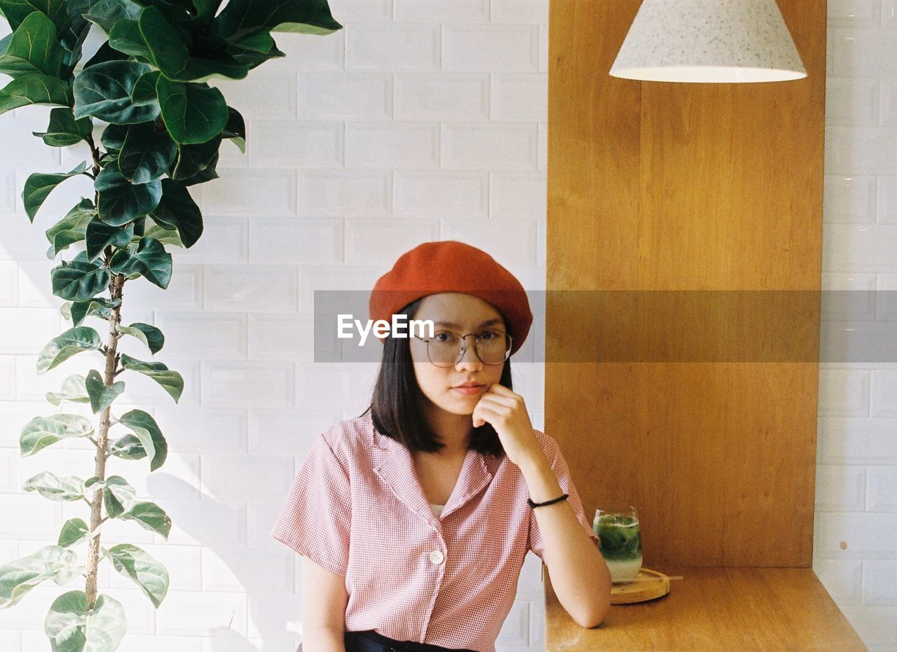 one person, real people, lifestyles, front view, wall - building feature, indoors, young women, waist up, young adult, food and drink, table, restaurant, holding, leisure activity, sitting, looking, casual clothing, plant, portrait, contemplation, glass