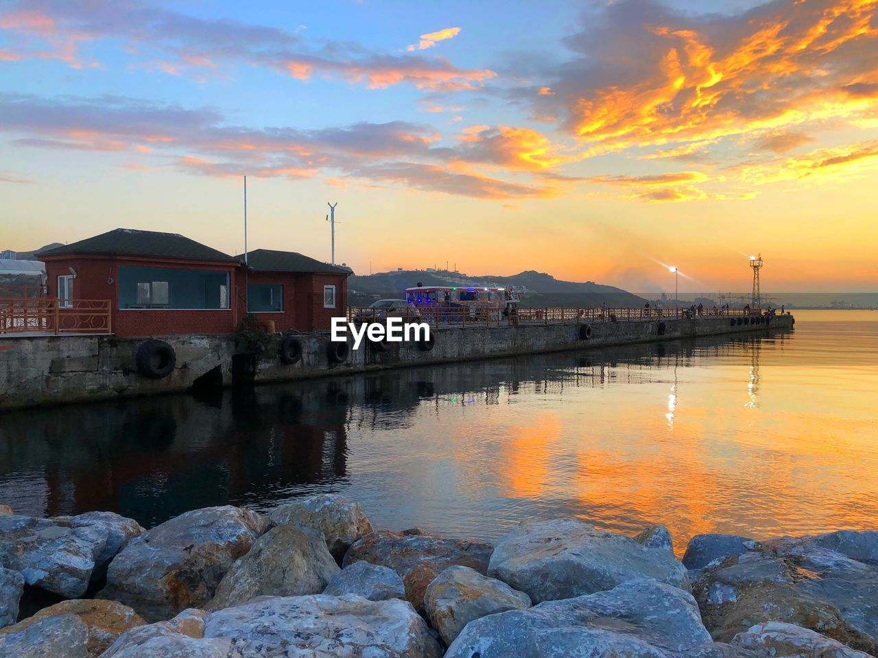 water, sky, sunset, built structure, architecture, building exterior, cloud - sky, orange color, reflection, sea, nature, building, beauty in nature, scenics - nature, rock, rock - object, solid, no people, tranquility, outdoors, bay