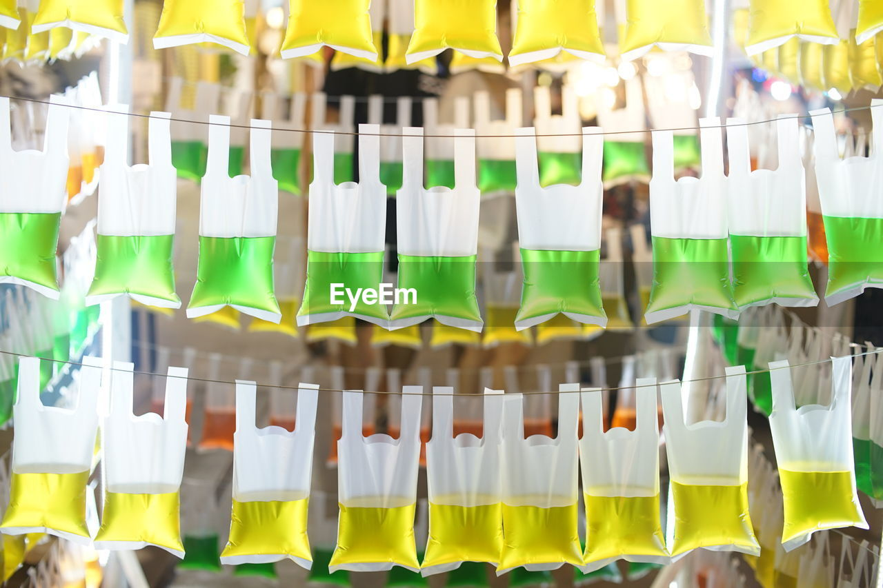 side by side, multi colored, choice, in a row, large group of objects, no people, variation, food and drink, flag, indoors, arrangement, celebration, green color, retail, abundance, refreshment, day, drink, hanging, focus on foreground, retail display