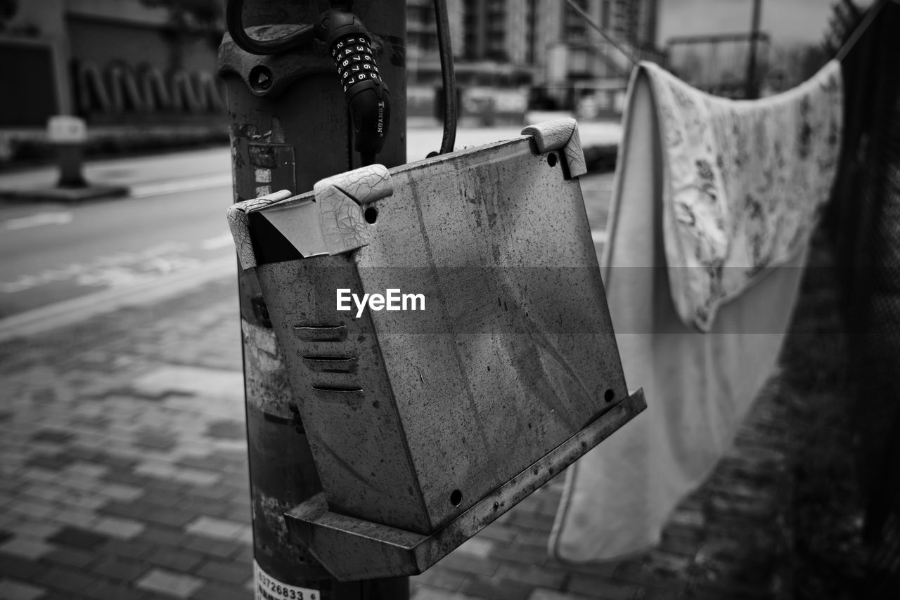 focus on foreground, metal, hanging, no people, close-up, architecture, city, day, street, selective focus, old, outdoors, built structure, security, protection, abandoned, building exterior, footpath, nature, water