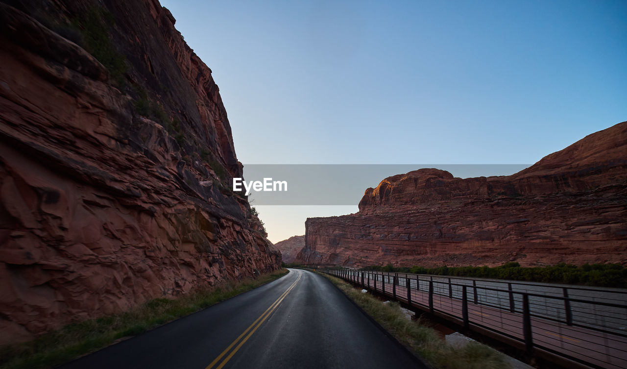 road, transportation, sky, mountain, the way forward, direction, nature, no people, diminishing perspective, symbol, clear sky, day, rock, scenics - nature, beauty in nature, rock formation, road marking, non-urban scene, rock - object, rocky mountains, formation, mountain range, outdoors, dividing line