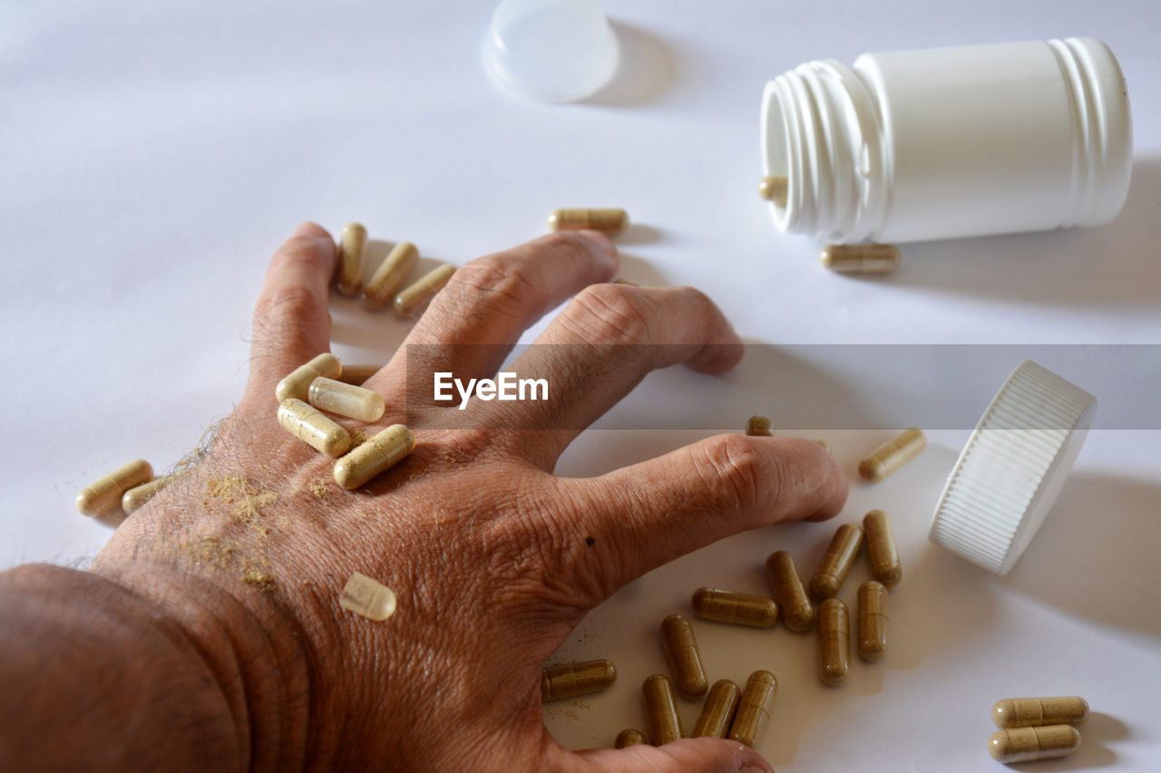 Close-up of hand with capsules on table