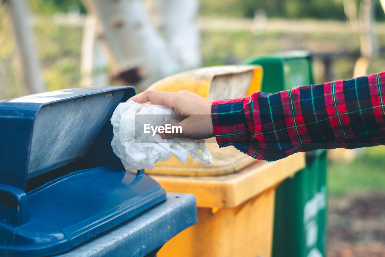 focus on foreground, holding, one person, day, real people, human hand, lifestyles, recycling, garbage, hand, garbage bin, human body part, recycling bin, outdoors, container, plastic, hygiene, midsection, environmental issues, plastic bag