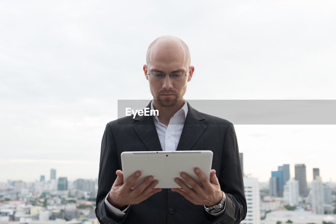 MAN USING PHONE WHILE STANDING ON CITY