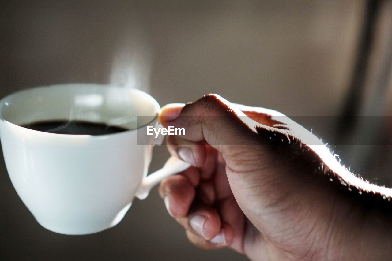 human hand, cup, hand, drink, mug, food and drink, coffee cup, human body part, refreshment, real people, coffee, coffee - drink, one person, indoors, holding, lifestyles, close-up, focus on foreground, unrecognizable person, finger, crockery, tea cup
