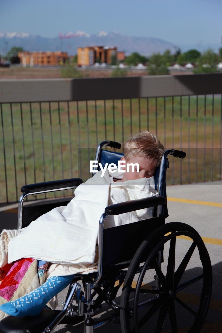 Boy Sleeping In Sitting On Wheel Chair