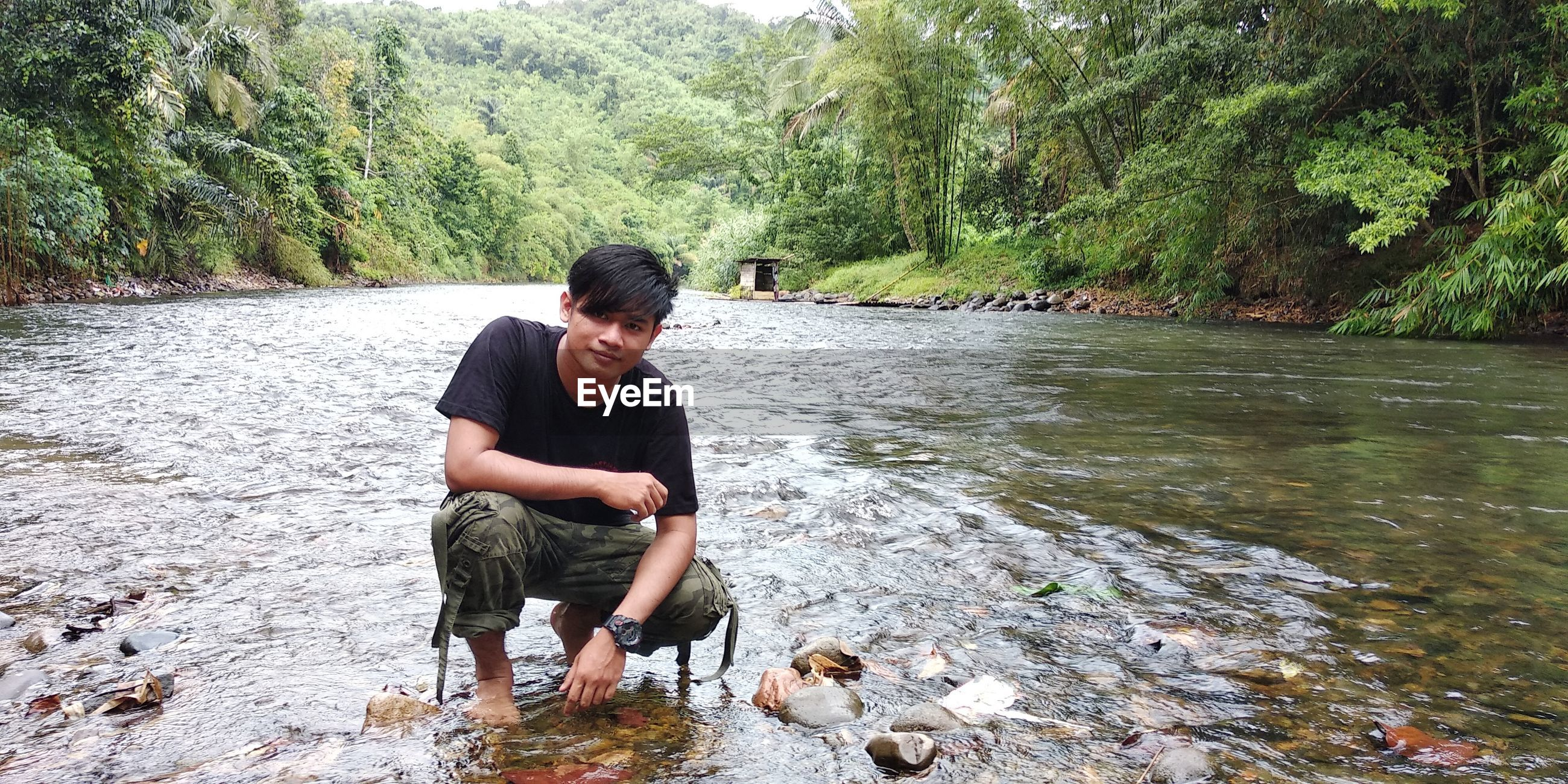 water, rock, one person, river, real people, casual clothing, rock - object, nature, solid, lifestyles, plant, day, tree, leisure activity, full length, beauty in nature, men, flowing water, outdoors, adolescence, teenager, stream - flowing water