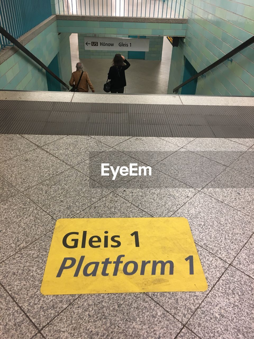text, communication, sign, western script, yellow, architecture, day, tile, high angle view, built structure, tiled floor, outdoors, flooring, script, no people, non-western script, warning sign, information, information sign, message