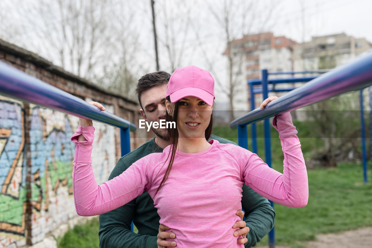 Portrait Of Young Woman With Boyfriend Exercising At Park